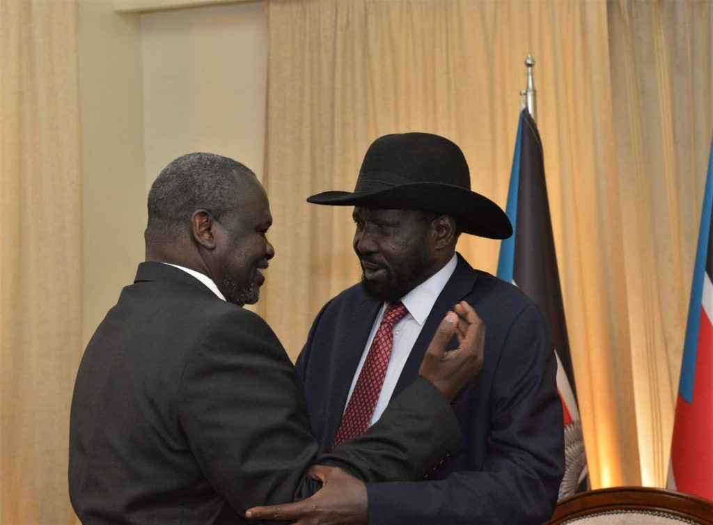 South Sudan president, Salva Kiir Mayardit, and First Vice President Dr. Riek Machar Teny, greeting each other during Machar's swearing in ceremony in February [Photo via Reuters]