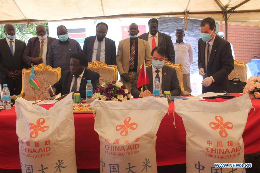 Manasseh Lomole (L, Front), chairperson of SSRRC and Chinese Ambassador to Juba  Hua Ning (R, Front) sign documents during a handover ceremony of food aid in Juba, South Sudan, on Sept. 17, 2020. [Photo by Xinhua]