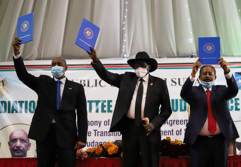 Sudan's Sovereign Council Chief Abdel Fattah al-Burhan, South Sudan's President Salva Kiir, and Sudan's Prime Minister Abdalla Hamdok lift copies of the peace agreement with the country's rebel groups in Juba, South Sudan, August 31. [Photo by REUTERS]