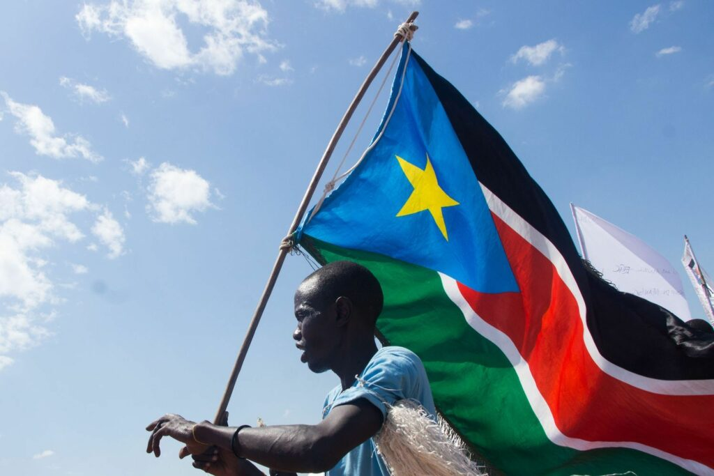 A man carries South Sudan's national flag at Mangateen Internal Displaced persons (IDPs) center during the visit of South Sudan's vice president in Juba on Nov. 17, 2018. [Photo by Akuot Chol/AFP/GETTY IMAGES
