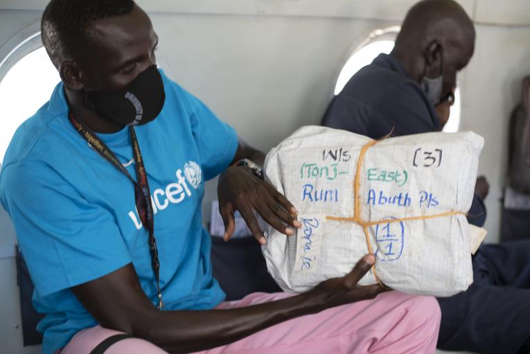 A UNCEF team on a helicopter transporting examination papers [Photo by UNICEF]