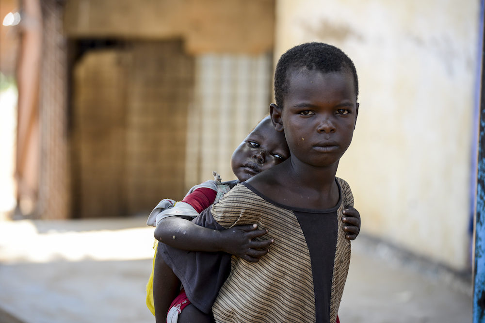 A child carries his younger sister on his back. Both children are living on the street in Aweil, South Sudan [Photo by UNICEF]